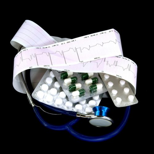 stethoscope and cardiogram with pill against black background